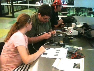 'Hack The Evening' attracts people from a high diversity of age, socio-cultural and educational backgrounds as well as interests and areas of expertise. Placed in a library setting, the group provides social learning opportunities between people that would probably not have met otherwise. The picture shows an electronics 'geek' teaching a school kid how to solder.
